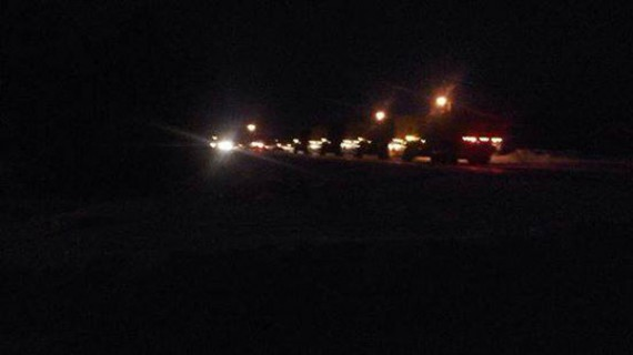 Trucks and police vehicles arriving at site of crash